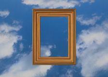 Heavenly picture. Wooden pictureframe on a clouds background Stock Photos