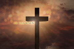 Heavenly scene with Jesus Christ wooden cross elevated on the sky and He has risen text on a sunset background Stock Photo