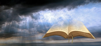 Heavenly spiritual light. Photo of an open holy bible set against a stormy cloud sky with sun rays shining onto bible stock photos