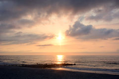 Heavenly Summer Sunrise Over Rock Jetty on the Beach Royalty Free Stock Photo