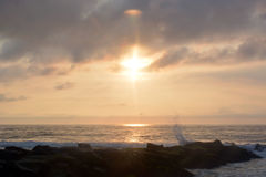 Heavenly Summer Sunrise Over Rock Jetty on the Beach Royalty Free Stock Images