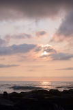 Heavenly Summer Sunrise Over Rock Jetty on the Beach Stock Photography