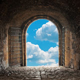 Heavens Gate. A dark corridor with a arch opening to a beautiful cloudy sky Royalty Free Stock Images