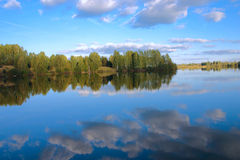 Heavens in water. Sky reflexion in a pond surrounded with trees removed in the autumn afternoon Royalty Free Stock Photo