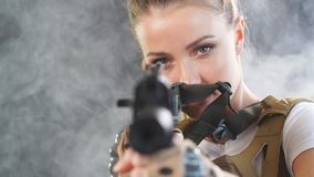 Heavily armed female soldier in battle helmet holding assault rifle. Heavily armed and well-equipped female soldier in battle helmet holding assault rifle stock video