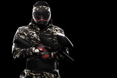 Heavily armed masked paintball soldier isolated on black background. Ad concept. Copy space royalty free stock photo