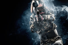 Heavily armed masked paintball soldier isolated on black background. Ad concept. Copy space royalty free stock image