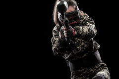 Heavily armed masked paintball soldier isolated on black background. Ad concept. Royalty Free Stock Photography