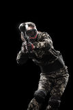 Heavily armed masked paintball soldier isolated on black background. Ad concept. Stock Images