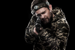 Heavily armed masked paintball soldier isolated on black background. Ad concept. Stock Photos