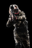 Heavily armed masked paintball soldier isolated on black background. Ad concept. Stock Photography