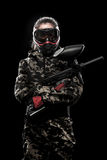 Heavily armed masked paintball soldier isolated on black background. Ad concept. Royalty Free Stock Photo