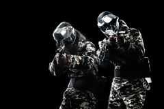 Heavily armed masked paintball soldier isolated on black background. Ad concept. Copy space royalty free stock photos