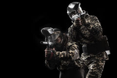 Heavily armed masked paintball soldier isolated on black background. Ad concept. Stock Image