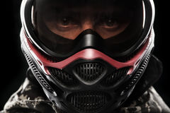 Heavily armed masked paintball soldier isolated on black background. Ad concept. Copy space stock photography