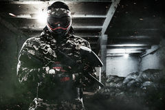 Heavily armed masked paintball soldier on post apocalyptic background. Ad concept. stock photography