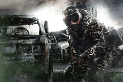 Heavily armed masked paintball soldier on post apocalyptic background. Ad concept. royalty free stock photo