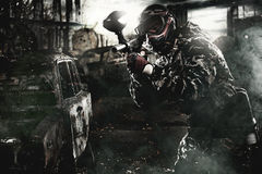 Heavily armed masked paintball soldier on post apocalyptic background. Ad concept. stock image