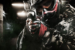 Heavily armed masked paintball soldier on post apocalyptic background. Ad concept. Heavily armed masked paintball soldier on black background. Ad concept. Copy stock photos