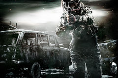Heavily armed masked paintball soldier on post apocalyptic background. Ad concept. royalty free stock photos