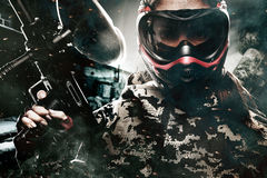 Heavily armed masked paintball soldier on post apocalyptic background. Ad concept. stock photos