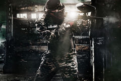 Heavily armed masked paintball soldier on post apocalyptic background. Ad concept. stock photo