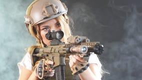 Heavily armed female soldier in battle helmet holding assault rifle. Slow motion. Heavily armed and well-equipped female soldier in battle helmet holding assault stock video