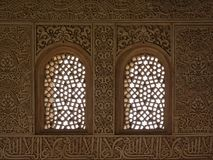 Heavily decorated wall with windows of Nasrid Palace , Alhambra, Spain. Heavily decorated wall with organic patterns and calligraphy and windows with stars and stock photo