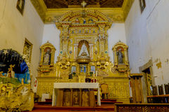Heavily golden religious decorated alter inside. QUITO, ECUADOR- AUGUST 4, 2015: Heavily golden religious decorated alter inside San Diego church shot from front Royalty Free Stock Photo