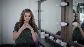 Heavily made girl with full lips sitting near mirror with lamps in the dressing room. She has long curly hair, which stock video