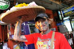 Heavily Tattooed Man Sells Flowers on Street. A heavily tattooed man sells flowers on Khaosan Road on Feb 25, 2012 in Bangkok, Thailand. Thai Yantra tattoos are royalty free stock photography