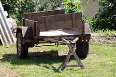 Heavily used old car trailer with rusted metal and wooden parts left on grass in backyard surrounded with building material and. Trees in background stock photography