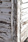 Heavily weathered wood with flaked white paint in closeup. The corner of an old wooden house Stock Photo
