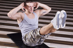 Heavy abs exercise. Fitness instructor doing Heavy abs exercise on the floor of the gym Stock Photo