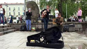 Heavy applause for honest street musicians playing guitar and singing.