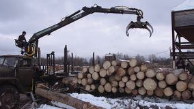 Heavy arm loader unloads lumber logs from heavy truck at sawmill factory. Cold cloudy winter day stock video