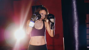 A heavy bag boxing exercise by a young woman. A strong woman starts jabbing heavily on a punching bag stock video footage