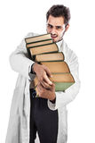 Heavy books. A young and handsome doctor or medical student carrying a pile of ancient book Stock Images