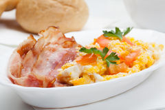 Heavy breakfast. Scrambled eggs with slices of bacon stock image