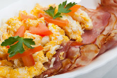 Heavy breakfast. Scrambled eggs with slices of bacon Royalty Free Stock Images