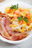 Heavy breakfast. Scrambled eggs with slices of bacon stock photography