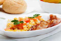 Heavy breakfast. Scrambled eggs with slices of bacon royalty free stock photography