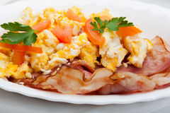 Heavy breakfast. Scrambled eggs with slices of bacon Stock Images