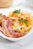 Heavy breakfast. Scrambled eggs with slices of bacon Stock Photo
