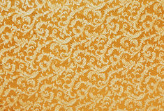 Heavy Brocade Fabric Background. Abstract background of a heavy golden brocade fabric with interwoven repeat design Stock Image