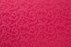 Heavy Brocade Fabric Background. Abstract background of a heavy red brocade fabric with interwoven repeat design Stock Photo