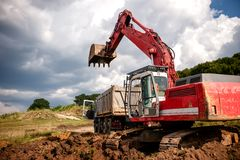 Heavy bulldozer and excavator loading and moving red sand Stock Photo
