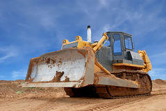 Heavy bulldozer with half raised blade in sandpit Stock Photography