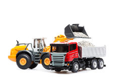 The heavy bulldozer and heavy truck. The heavy bulldozer of yellow color on a white background is loading of heavy dump-body truck Royalty Free Stock Photography