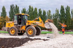 Heavy bulldozer loading and moving gravel on road construction site Stock Images